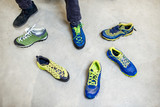 Man trying different trail shoes for mountain hiking in the sports shop, close-up view with no face
