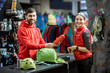 Portrait of a young woman as a customer with salesman at the counter of the sports shop