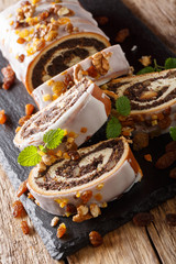 Delicious poppy seed roll with raisins and walnuts covered with glaze close-up. vertical