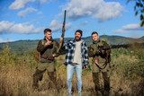 Activity for real men concept. Hunters gamekeepers looking for animal or bird. Hunters with rifles in nature environment. Illegal hunting. Hunters friends enjoy leisure. Poacher partner in crime - 243663408
