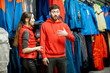 Man and woman as a sellers or clients talking together in the sports department with skiing clothes in the shop