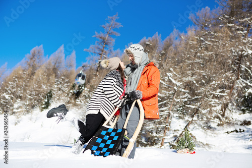Loving couple together on a winter vacation while sledding