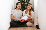 Happy young couple sitting at the christmas tree - 243669294