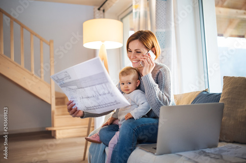 A young woman with a toddler daughter sitting indoors, working at home.