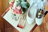bridal accessories such as shoes, bouquet , garter and perfume lie on a chair