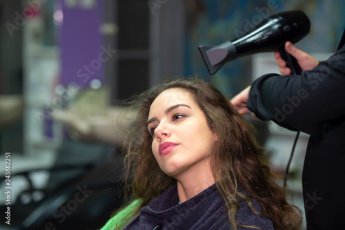 young woman in hairdresser salon drying hair
