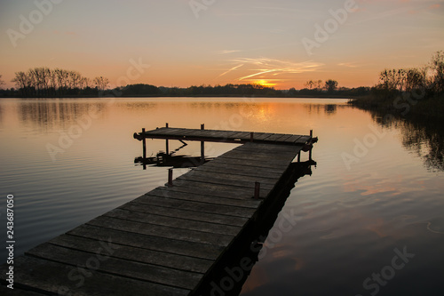 Acrylglas Pier Jetty on a calm lake and the sky during sunset.