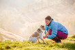 Leinwandbild Motiv woman playing with her dog in beautiful mountain scenery in spring