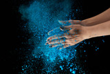 cropped view of adult woman holding blue holi powder and clapping on black background - 243697479