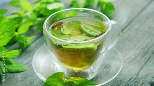 From above view of glass cup of green tea with leaves of mint and slice of lemon placed on saucer on wooden background