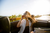Woman uses mobile phone and siting in cabriolet at summer day - 243702036