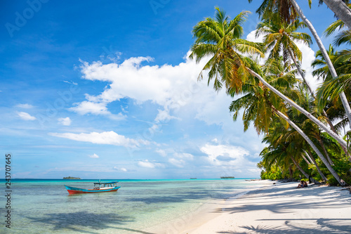 A nice and empty beach in a tropical desert island of Pulau Banyak, Sumatra, Indonesia. Blue sky, white sand and coconut trees, a dream holiday place to relax, snorkel and rest.