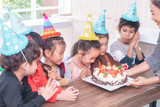 Group of children is blowing birthday cake in birthday  party singing happy birthday - 243709461