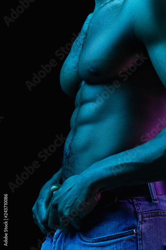 Close up portrait of a young naked african man at studio. High Fashion male model in colorful bright lights posing on black background. Art design concept