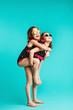 Quadro Girl in swimwear giving piggyback ride to her friend