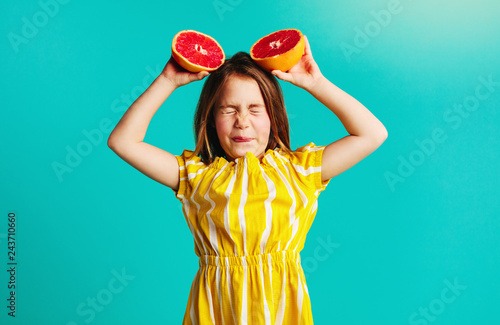 Girl holding grapefruit with dislike expressions