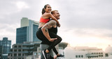 Cheerful man carrying a fitness woman on his back walking on roo - 243713425
