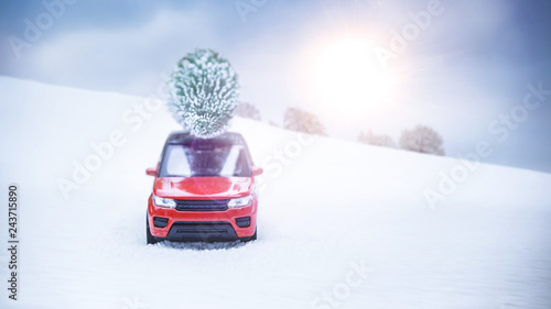 Fridge magnet Ein rotes Auto fährt mit einem Weihnachtsbaum auf dem Dach durch eine Winterlandschaft. Die Sonne scheint. Lens Flares.