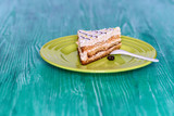 Biscuit cake on a wooden background photographed on a ceramic plate in green. - 243721658