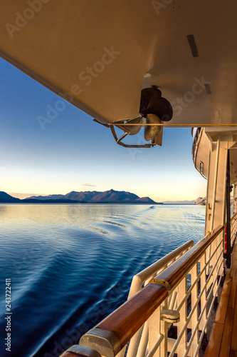 Beautiful golden early morning light of dawn and ocean water ripples from ship's wake, Inside Passage, Alaska, USA.