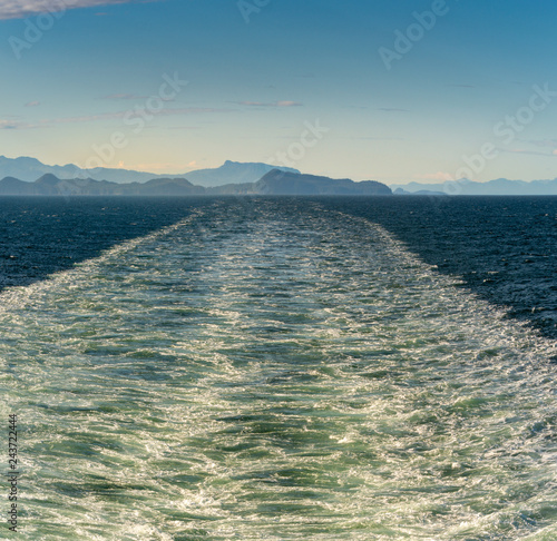 Sunny bright panorama of turbulent ship wash in the vast ocean channel of Stephen's Passage, Alaska, USA Inside Passage.