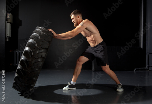 Poster Crossfit training - man flipping tire