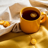 Cup with tea kumquat on yellow background