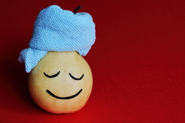 Spa salon. Relaxed happy yellow pear with blue towel on red background. Art idea.