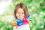 Little girl showing painted hands on  background - 243734642