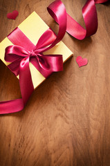 White gift box and red ribbon with tag on wood background. Vintage gift box on wooden board with space for text. © Belight