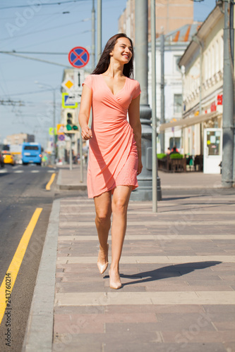 Portrait in full growth, young beautiful brunette woman in pink dress