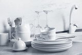 Set of clean dishes and cutlery on kitchen counter