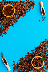 Brown roasted coffee beans scattered on blue background top view mockup © 9dreamstudio