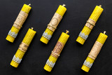 Buddhism. Candles with Yantras and mantras in sanskrit on black background top view pattern