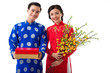 Happy young Asian couple holding traditional Tet symbols: blooming apricot branches and red and golden giftboxes