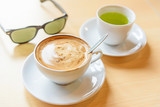 hot cappuccino coffee with green tea and sunglasses on table
