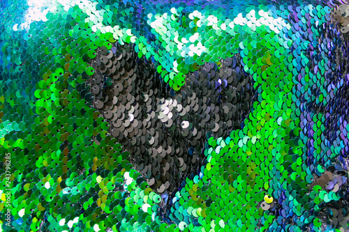 Sequins close-up macro. Abstract background with colorful sequins color on the fabric. Texture scales of round sequins with color transition.