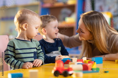 Leinwandbild Motiv nursery children building blocks with a teacher in preschool playroom