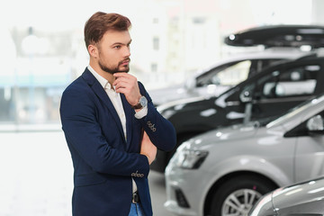 The buyer of the car thinks in the car dealership.