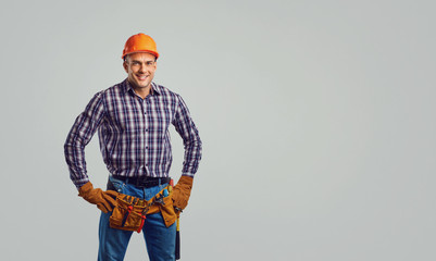 Repairman in special clothes on a gray background. © Studio Romantic
