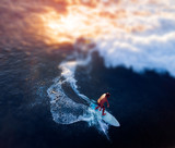 Fototapeta Zachód słońca - Aerial view of the young man surfs the wave at sunset. Tilt shift effect applied © Dudarev Mikhail