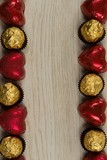 Chocolates and heart shape decorations arranged on wooden table - 243824652