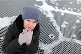 The woman's portrait in winter clothes against the background of a lattice from the fountain. A look with top - 243828649