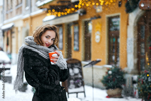 Wall mural Winter outdoor portrait of adorable brunette woman drinking coffee at the street. Empty space