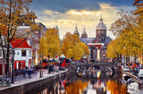 Fototapeta Panele - Amsterdam, Netherlands. Autumn sunset in Red-light district. © Yasonya