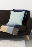 Cushions and blanket arranged on sofa - 243844453