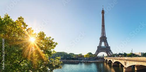 Leinwandbild Motiv Paris street with view on the famous paris eiffel tower on a sunny day with some sunshine