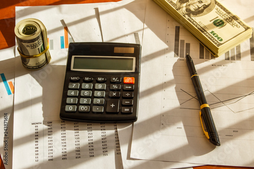 Bundle of dollars and calculator on the table in the office © semenyaka