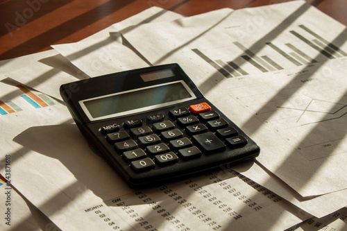 Calculator with papers on the office table © semenyaka