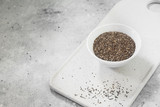 Chia seeds for healthy eating. In a white bowl. On grey background - 243874052